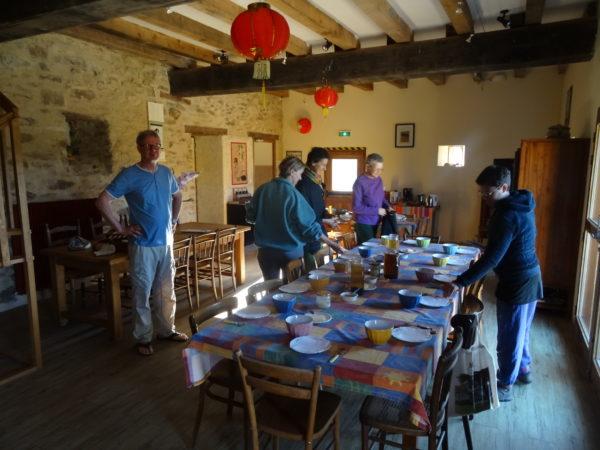 Préparation collective du petit déjeuner, dans la salle à manger