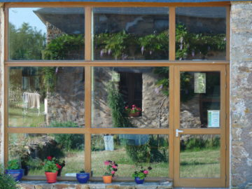 Façade ouest en reflet dans la véranda de la bibliothèque